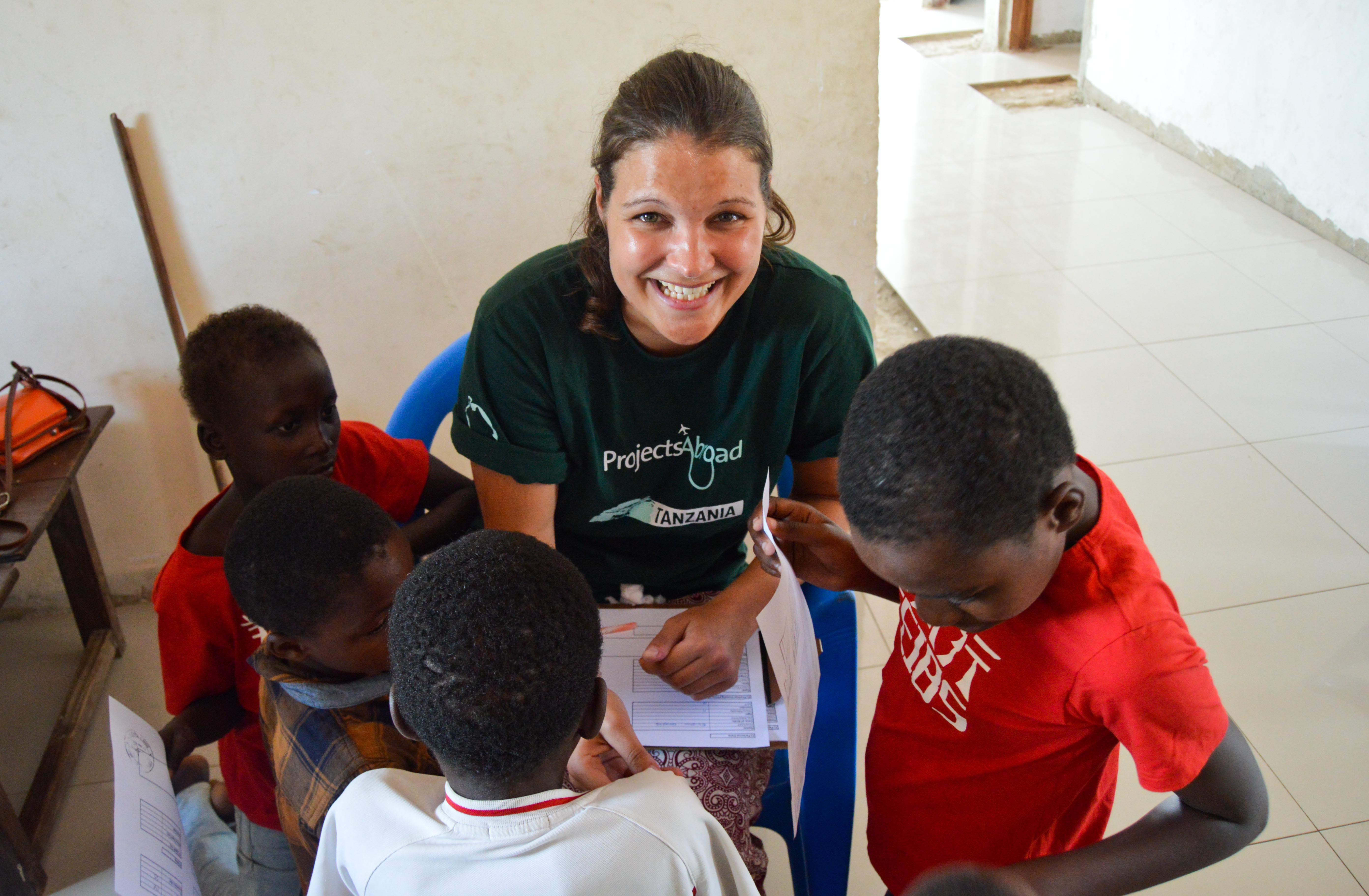 Female intern from Projects Abroad is pictured screening children during her nursing internship in Tanzania.